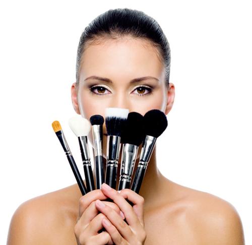 Mujer con brochas de maquillaje en la mano