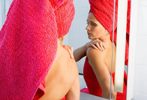Mujer mirándose los lunares en el espejo