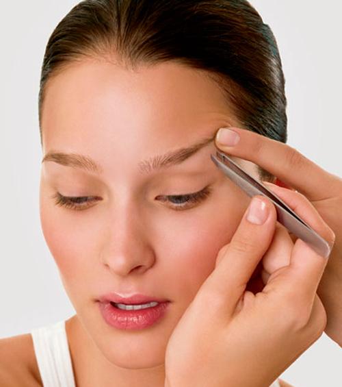 Mujer depilándose las cejas