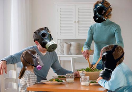 Foto de una familia sentada a la mesa con máscaras antigás