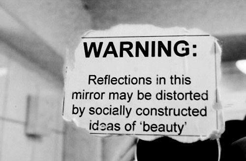 """Advertencia: El reflejo en este espejo podría estar distorsionado por """"conceptos de belleza"""" construidos por la sociedad."""
