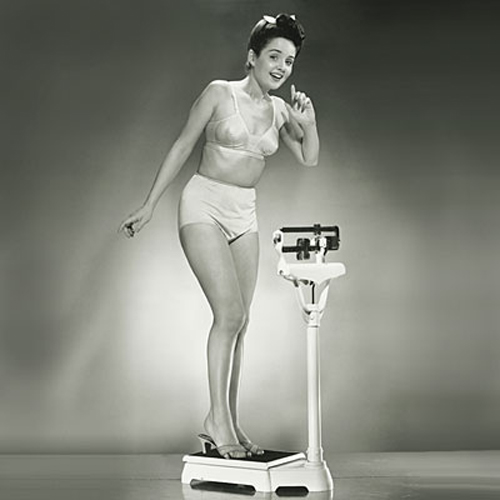 Woman standing on weighing scales, portrait