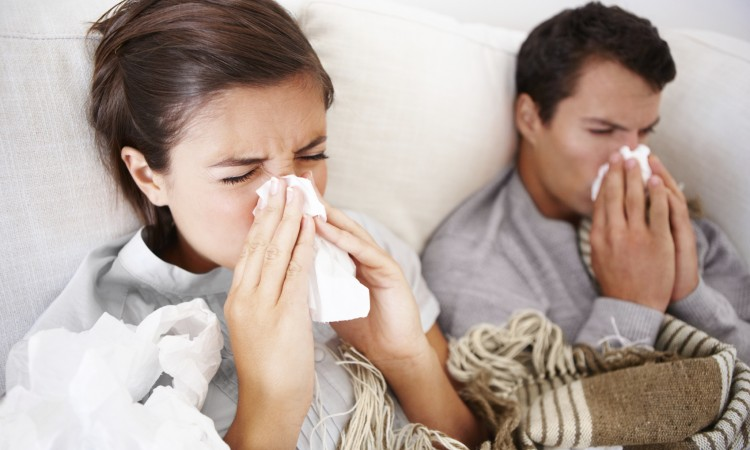 Young couple frighting the flu as they both lie in bed