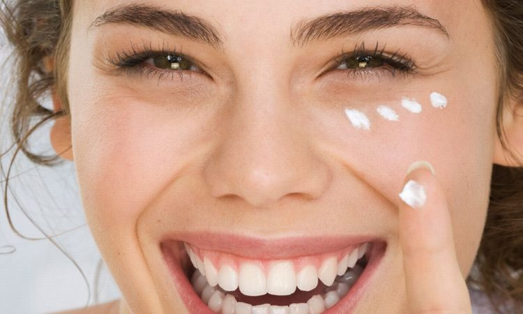 Young Woman Putting Cream On Face Smiling
