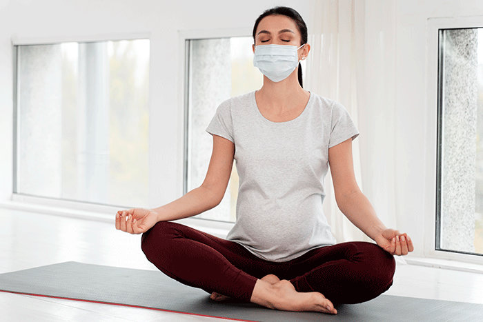 Pregnant Woman With Medical Mask Meditating (1)