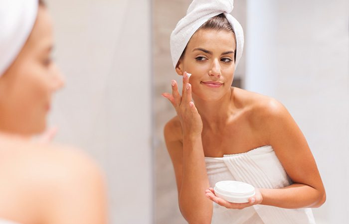 Gorgeous Woman Applying Moisturizer On Face