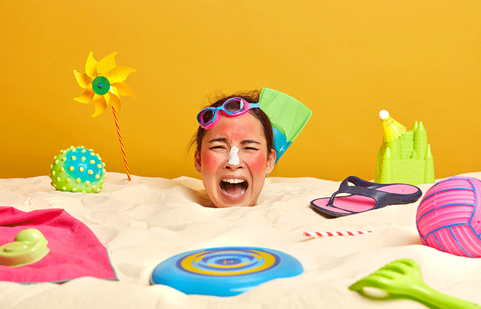 Young Woman Head With Sunscreen Cream On Face Surrounded By Beach Accessories (1)